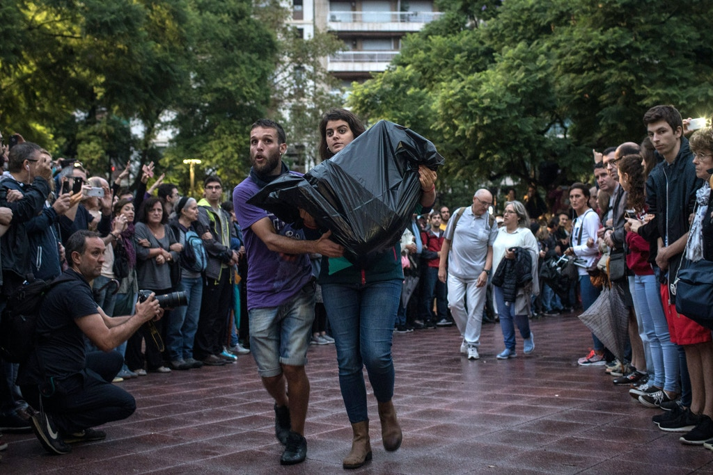BARCELONA, SPAIN - OCTOBER 01: Two people bring in ballot boxes as crowds gather outside Escola Industrial of Barcelona school on October 1, 2017 in Barcelona, Spain. More than five million eligible Catalan voters are estimated to visit 2,315 polling stations today for Catalonia's referendum on independence from Spain. The Spanish government in Madrid has declared the vote illegal and undemocratic.  (Photo by Chris McGrath/Getty Images)
