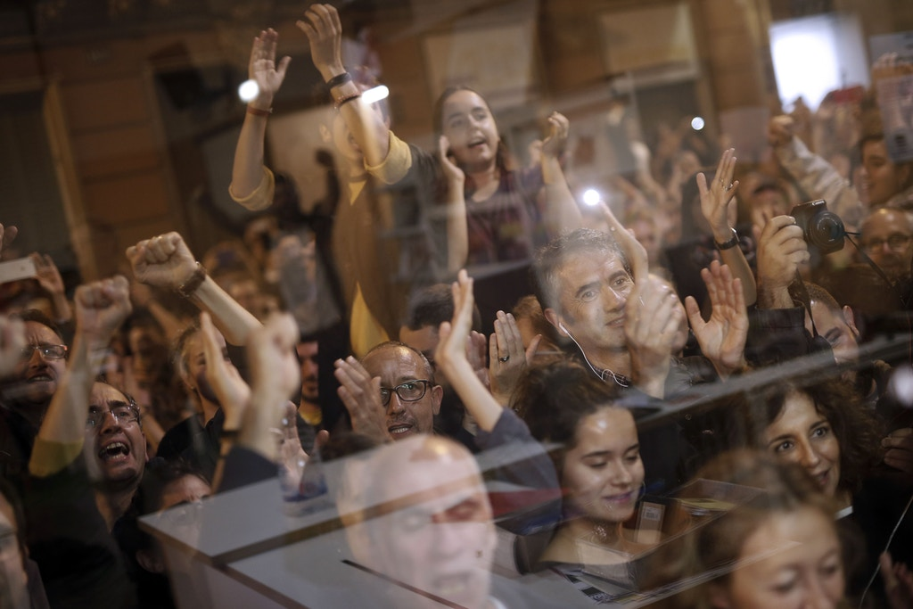 People celebrate after the closing of polling stations outside the 'Espai Jove La Fontana' (La Fontana youth center) on October 1, 2017 in Barcelona.Spanish riot police stormed voting stations today as they moved to stop Catalonia's independence referendum after it was banned by the central government in Madrid. At least 92 people were confirmed injured as hundreds tried to prevent the polling stations from being closed, Catalan officials said. A total of 465 people were treated at hospitals and health centres, while Spain's interior ministry said 12 police officers were injured. / AFP PHOTO / PAU BARRENA (Photo credit should read PAU BARRENA/AFP/Getty Images)