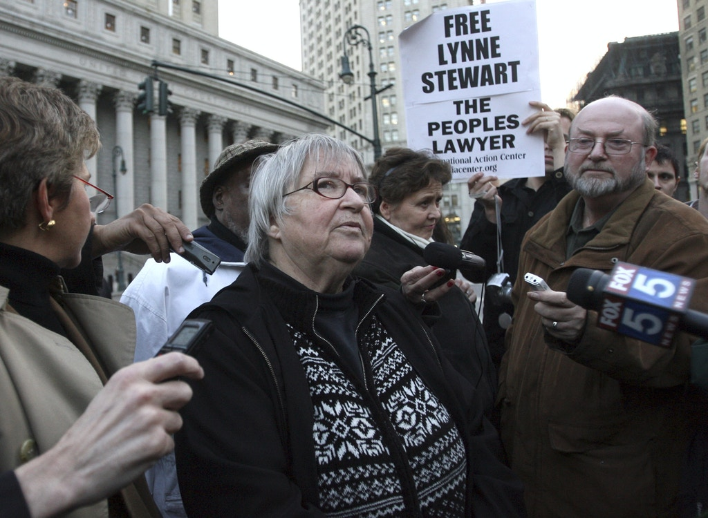 FILE - In this Nov. 17, 2009, file photo, Lynne Stewart, center, is surrounded by supporters and reporters in New York after a federal appeals court in New York City said a judge who sentenced Stewart to just over two years in prison should consider a harsher sentence in light of her case's terrorism connection. It can be an uncomfortable life for any defense attorney representing unpopular clients, but lawyers who agree to speak on behalf of people accused of plotting to kill Americans in terrorist attacks walk difficult road. Stewart was an attorney for a blind Egyptian sheik serving life for terrorism convictions until she was arrested on terrorism charges months after 9/11 for letting him communicate with followers. (AP Photo/Mary Altaffer, File)