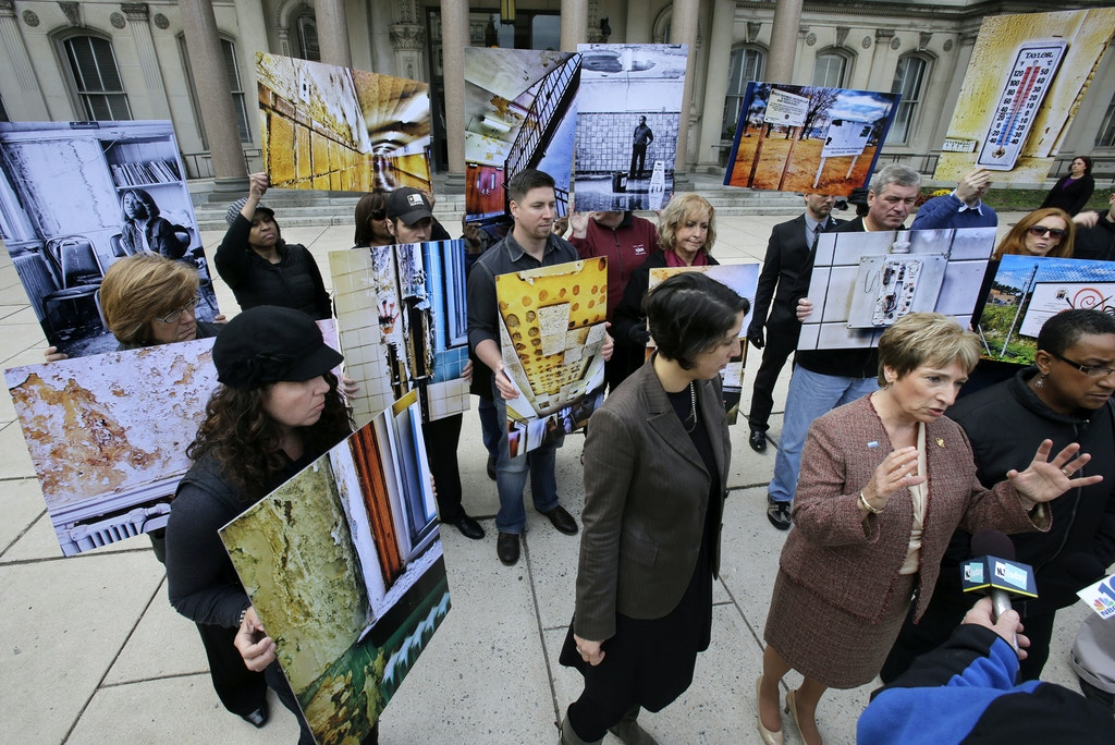 "Teacher and New Jersey Education Association vice president, Marie Blistan, second right, answers a question, as she stands in front of the Statehouse with others holding a display of photographs entitled ""A Blind Eye: the Immorality of Inaction,""   in Trenton, N.J., Wednesday, Oct. 23, 2013. The photos show crumbling ceilings, broken windows, peeling paint and other poor conditions in several public school systems, including in Trenton and Paterson. The coalition Healthy Schools Now is asking New Jersey to speed up the repair and replacement of run-down schools across the state. (AP Photo/Mel Evans)"