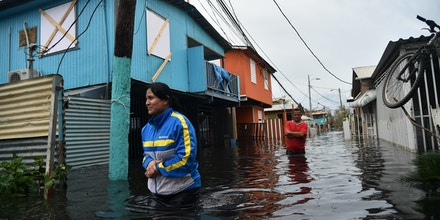 TOPSHOT - People walk accros a flooded street in Juana Matos, Puerto Rico, on September 21, 2017 as the country faced dangerous flooding and an island-wide power outage following Hurricane Maria. / AFP PHOTO / HECTOR RETAMAL        (Photo credit should read HECTOR RETAMAL/AFP/Getty Images)