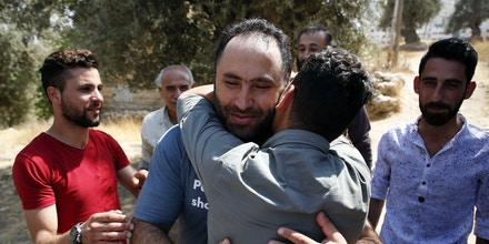 Prominent Palestinian activist Issa Amro is welcomed by supporters after he was released on bail by a Palestinian court, in the West Bank city of Hebron on September 10, 2017, following his prior arrest on September 4.Issa Amro was detained by Palestinian security forces in Hebron on accusations including causing strife, human rights activists say.His lawyer, Muhannad Karaja, said he has also been accused of creating websites that