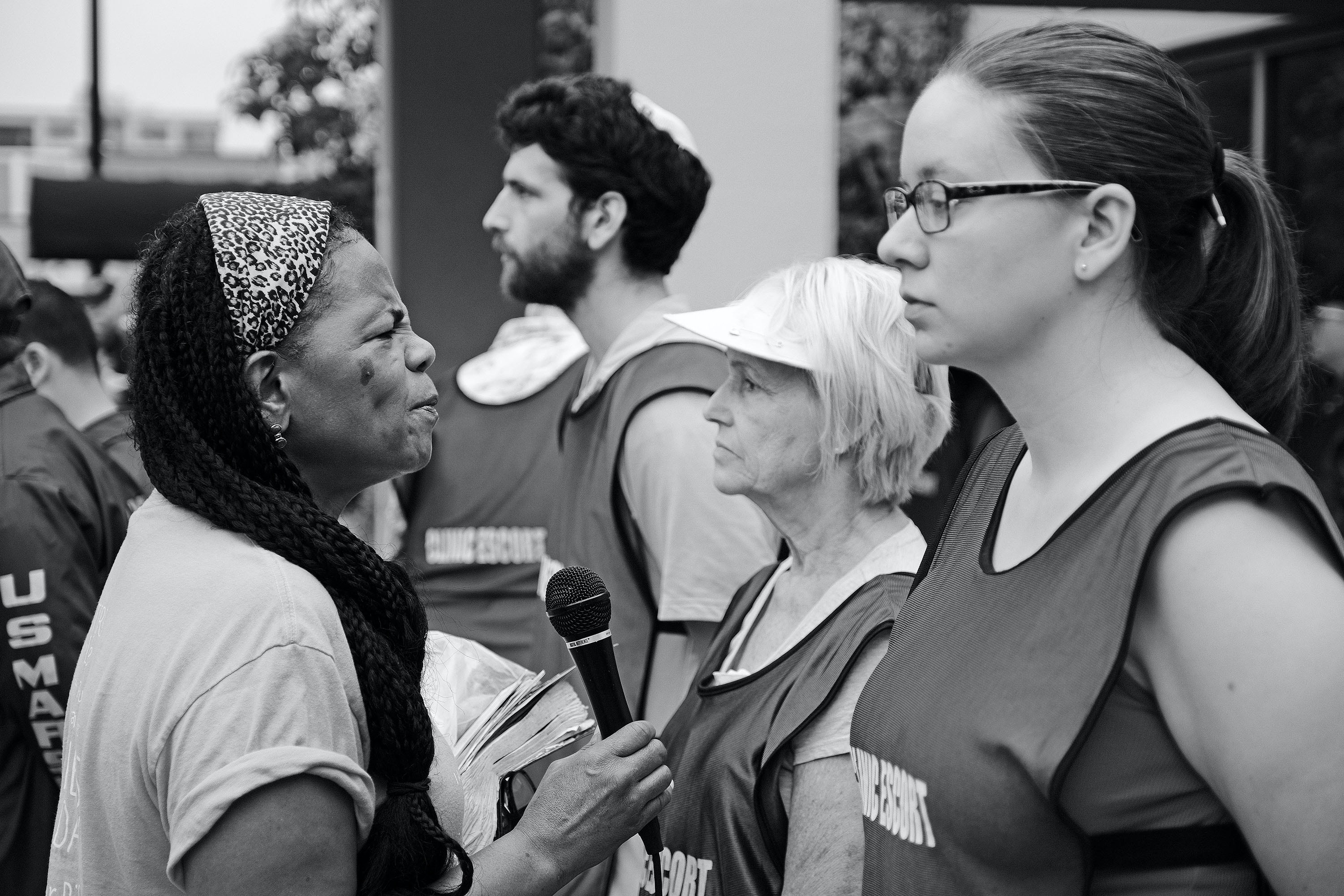 A protester from Sisters for Life uses a speaker system to berate clinic escorts and yell at clients through the walls of EMW Clinic. The clinic escorts practice non-engagement tactics in response.