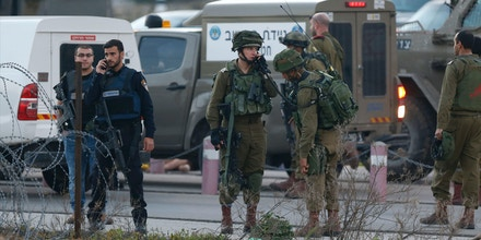 Israeli security forces monitor the area where a Palestinian man tried to stab Israeli soldiers before being shot dead at a checkpoint near Ramallah, in the occupied West Bank, on February 26, 2016. The Israeli army 'thwarted the attack, firing towards the assailant, resulting in his death,' it said in a statement. The Palestinian authorities did not immediately announce the identity of the attacker. Israeli media said the attack took place near the Beit El settlement outside Ramallah.