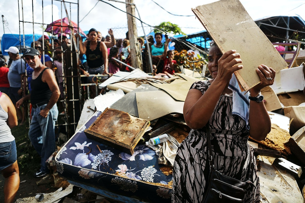 SAN ISIDRO, PUERTO RICO - OCTOBER 17:  A woman shields her face from the sun with a piece of wood as residents wait to receive food and water, provided by FEMA, in a neighborhood without grid electricity or running water on October 17, 2017 in San Isidro, Puerto Rico. The food and water delivery mission included U.S. Army, U.S. Coast Guard and Puerto Rico Hacienda forces. Residents said this was the first official governmental delivery of food and water to the community, nearly four weeks after the hurricane hit. Puerto Rico is suffering shortages of food and water in areas and only 17.7 percent of grid electricity has been restored. Puerto Rico experienced widespread damage including most of the electrical, gas and water grid as well as agriculture after Hurricane Maria, a category 4 hurricane, swept through.  (Photo by Mario Tama/Getty Images)