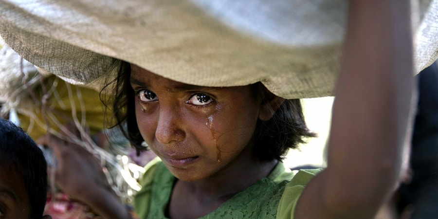 PALONG KHALI, BANGLADESH - OCTOBER 16: A Rohingya girl cries as refugees fleeing from Myanmar cross a stream in the hot sun on a muddy rice field on October 16, 2017 near Palang Khali, Cox's Bazar, Bangladesh. Well over a half a million Rohingya refugees have fled into Bangladesh since late August during the outbreak of violence in Rakhine state causing a humanitarian crisis in the region with continued challenges for aid agencies. (Photo by Paula Bronstein/Getty Images)