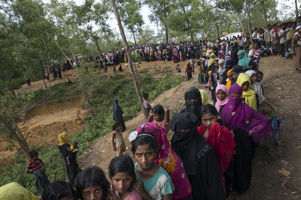 KUTUPALONG, BANGLADESH - OCTOBER 7: Rohingya wait in line for hours as an emergency food distribution takes place by World Food program ( WFP) and Save The Children October 7, Kutupalong, Cox's Bazar, Bangladesh. Rice, lentils, sugar, salt and oil was given out. Well over half a million Rohingya refugees have fled into Bangladesh since late August during the outbreak of violence in Rakhine state causing a humanitarian crisis in the region with continued challenges for aid agencies. (Photo by Paula Bronstein/Getty Images)