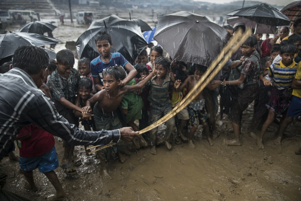 THAINKHALI, BANGLADESH - OCTOBER 7: A man hits anxious Rohingya children with a cane as things get out of control during a humanitarian aid distribution while monsoon rains continue to batter the area causing more difficulties October 7, Thainkhali camp, Cox's Bazar, Bangladesh. Well over half a million Rohingya refugees have fled into Bangladesh since late August during the outbreak of violence in Rakhine state causing a humanitarian crisis in the region with continued challenges for aid agencies. (Photo by Paula Bronstein/Getty Images)