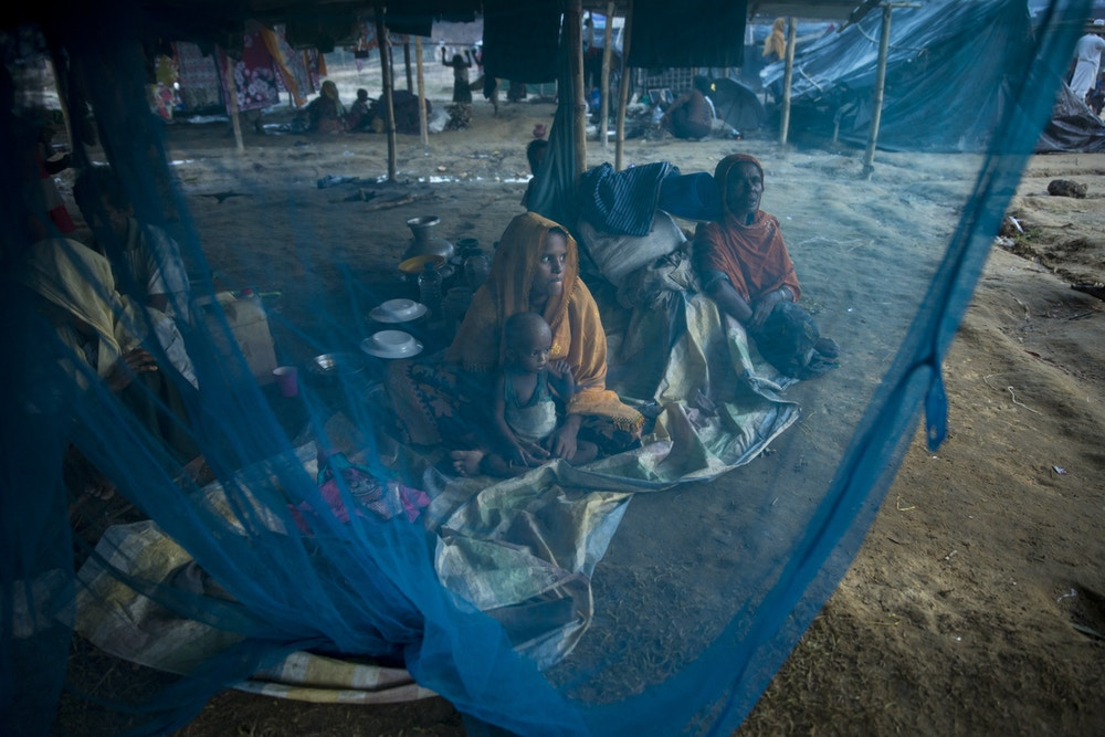 KUTUPALONG, BANGLADESH - SEPTEMBER 29: Women are seen behind a mosquito net September 29 in Kutupalong refugee camp, Bangladesh. Over a half a million Rohingya refugees have fled into Bangladesh from the horrific violence in Rakhine state in Myanmar causing a humanitarian crisis. (Photo by Paula Bronstein/Getty Images)