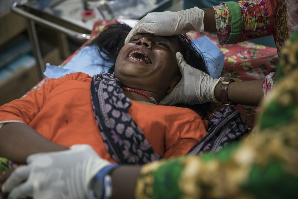 KUTUPALONG, BANGLADESH - OCTOBER 4: Aneta Begum,25, is treated for a head injury by staff member Jacqueline Murekezi at the 'Doctors Without Borders' Kutupalong clinic on October 4, 2017 in Cox's Bazar, Bangladesh. Doctors Without Borders has been providing comprehensive basic healthcare services at their Kutupalong clinic since 2009. Due to the current Rohingya crisis, the clinic has expanded it's inpatient capacity dealing with approximately 2,500 out patient treatments and around 1,000 emergency room patients per week. All healthcare services provided at the clinic are free of charge to both the Rohingya refugee population as well as local Bangladeshi patients. Doctors Without Borders has also set up a number of health posts, mobile clinics and water and sanitation services elsewhere in Cox's Bazar to better respond to the influx. Well over a half a million Rohingya refugees have fled into Bangladesh since late August during the outbreak of violence in Rakhine state causing a humanitarian crisis in the region with continued challenges for aid agencies. (Photo by Paula Bronstein/Getty Images)