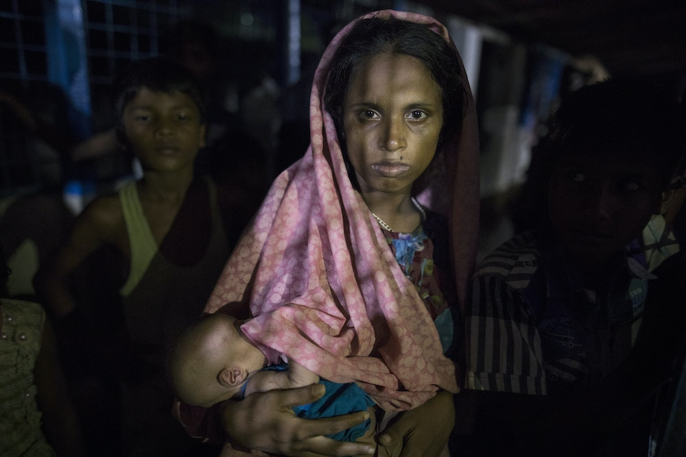 KUTUPALONG, BANGLADESH - SEPTEMBER 29:  Hasina Begum, age 18, holds her newborn baby, 8 days old,  born while she was walking in the forest escaping from Myanmar September 29, 2017 in Kutupalong , Bangladesh. She is now living inside a makeshift shelter packed with new arrivals. Over a half a million Rohingya refugees have fled into Bangladesh from the horrific violence in Rakhine state in Myanmar causing a humanitarian crisis. (Photo by Paula Bronstein/Getty Images)