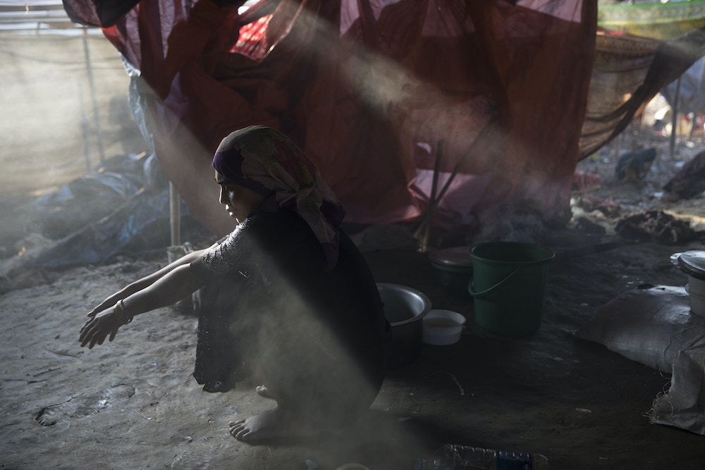 THAINKHALI, BANGLADESH - SEPTEMBER 25:  Sajida Begum, 18, sits in her makeshift tent, washing rice for dinner as smoke catches the late afternoon light September 25, 2017 in Thainkhali camp, Cox's Bazar, Bangladesh. Over 429,000 Rohingya refugees have fled into Bangladesh since late August during the outbreak of violence in Rakhine state as Myanmar's de facto leader Aung San Suu Kyi downplayed the crisis during a speech in Myanmar this week faces and defended the security forces while criticism on her handling of the Rohingya crisis grows. Bangladesh's prime minister, Sheikh Hasina, spoke at the United Nations General Assembly last week, focusing on the humanitarian challenges of hosting the minority Muslim group who currently lack food, medical services, and toilets, while new satellite images from Myanmar's Rakhine state continue to show smoke rising from Rohingya villages.  (Photo by Paula Bronstein/Getty Images)