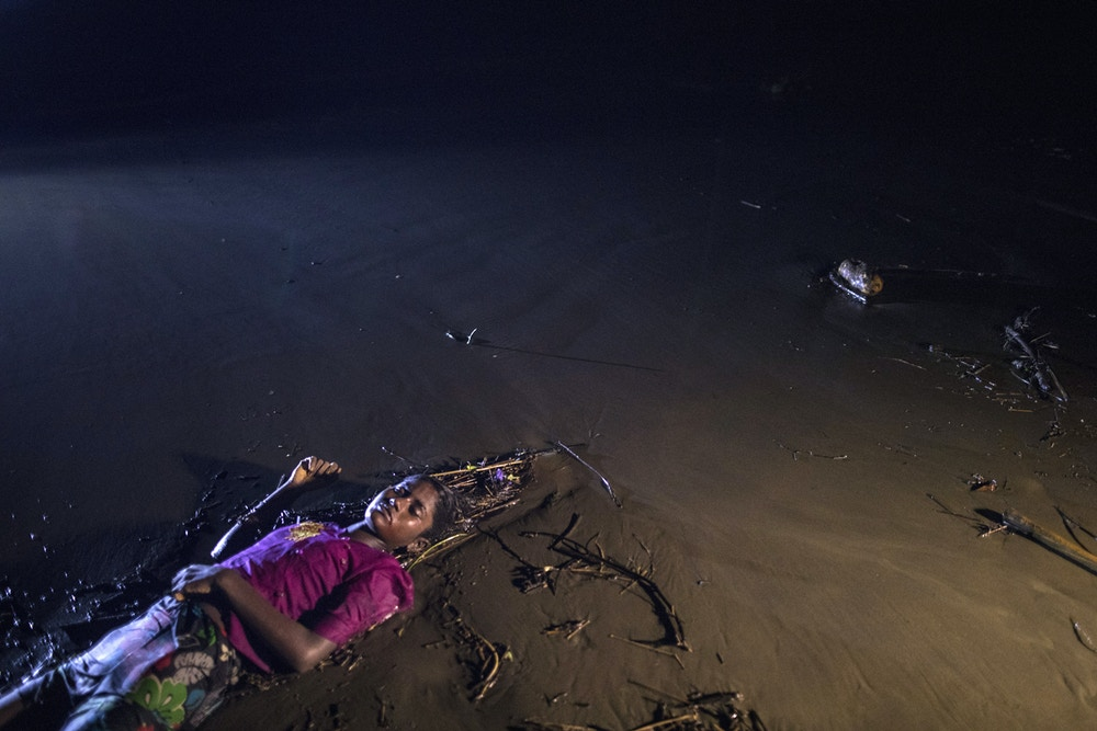 PATUWARTEK, INANI BEACH, BANGLADESH - SEPTEMBER 28: (EDITORS NOTE: Image depicts death.) The body of a Rohingya woman lays on a beach washed up after a boat sunk in rough seas off the coast of Bangladesh carrying over 100 people September 28 close to Patuwartek, Inani beach, Bangladesh. Seventeen survivors were found along with the bodies of 15 women and children. Over 500 Rohingya refugees have fled into Bangladesh since late August during the outbreak of violence in Rakhine state as Myanmar's de facto leader Aung San Suu Kyi downplayed the crisis during a speech in Myanmar this week faces and defended the security forces while criticism on her handling of the Rohingya crisis grows. Bangladesh's prime minister, Sheikh Hasina, spoke at the United Nations General Assembly last week, focusing on the humanitarian challenges of hosting the minority Muslim group who currently lack food, medical services, and toilets, while new satellite images from Myanmar's Rakhine state continue to show smoke rising from Rohingya villages.  (Photo by Paula Bronstein/Getty Images)