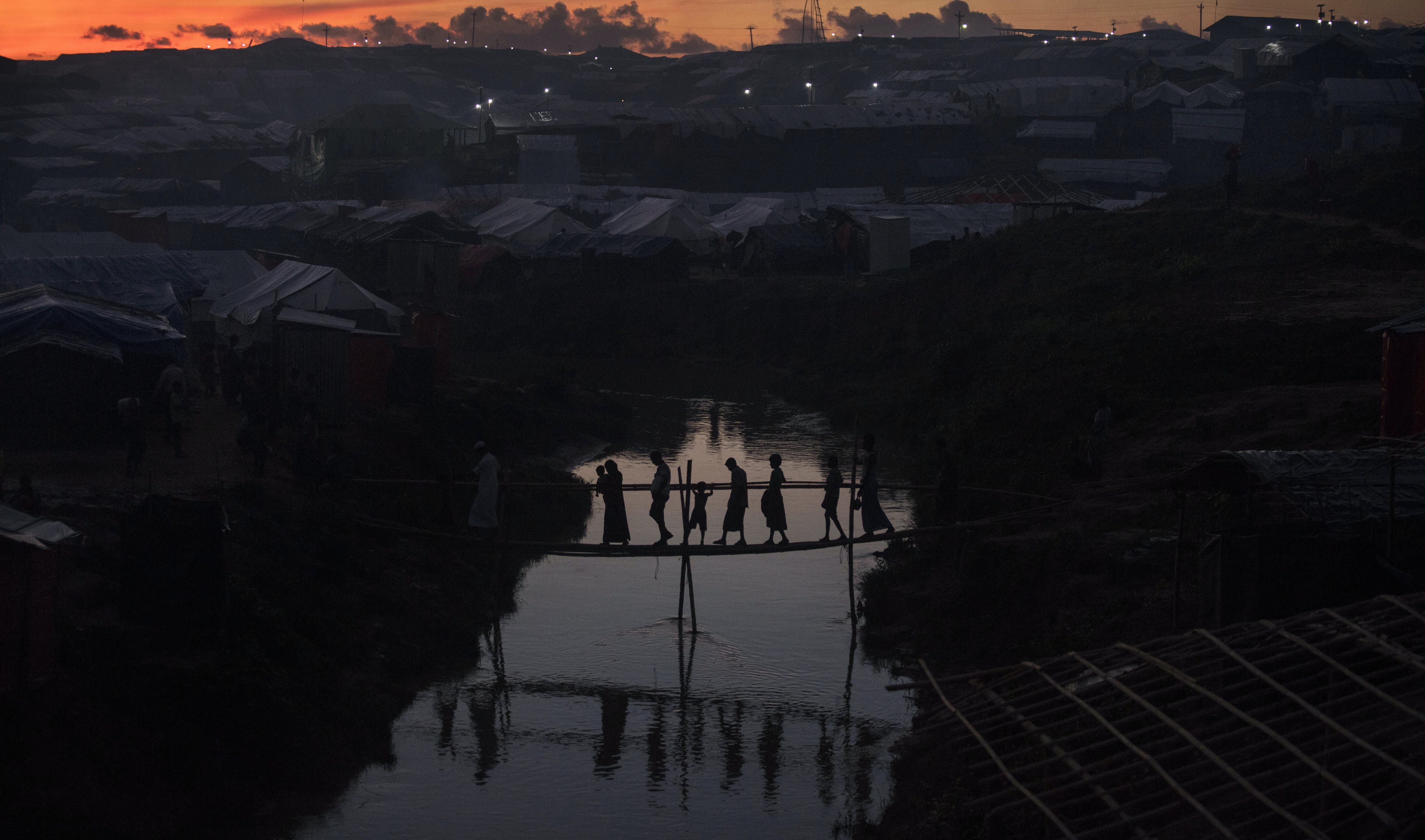 KUTUPALONG, BANGLADESH - OCTOBER 13: People cross a bamboo bridge over a stream as the sun sets on October 13, 2017 at the Kutuplaong refugee camp, Cox's Bazar, Bangladesh. According to UN sources around 519,000 Rohingya refugees had fled across the border from Myanmar to Bangladesh since 25 August. Thousands more remain stranded in Myanmar without the means to cross the border into Bangladesh. (Photo by Paula Bronstein/Getty Images)