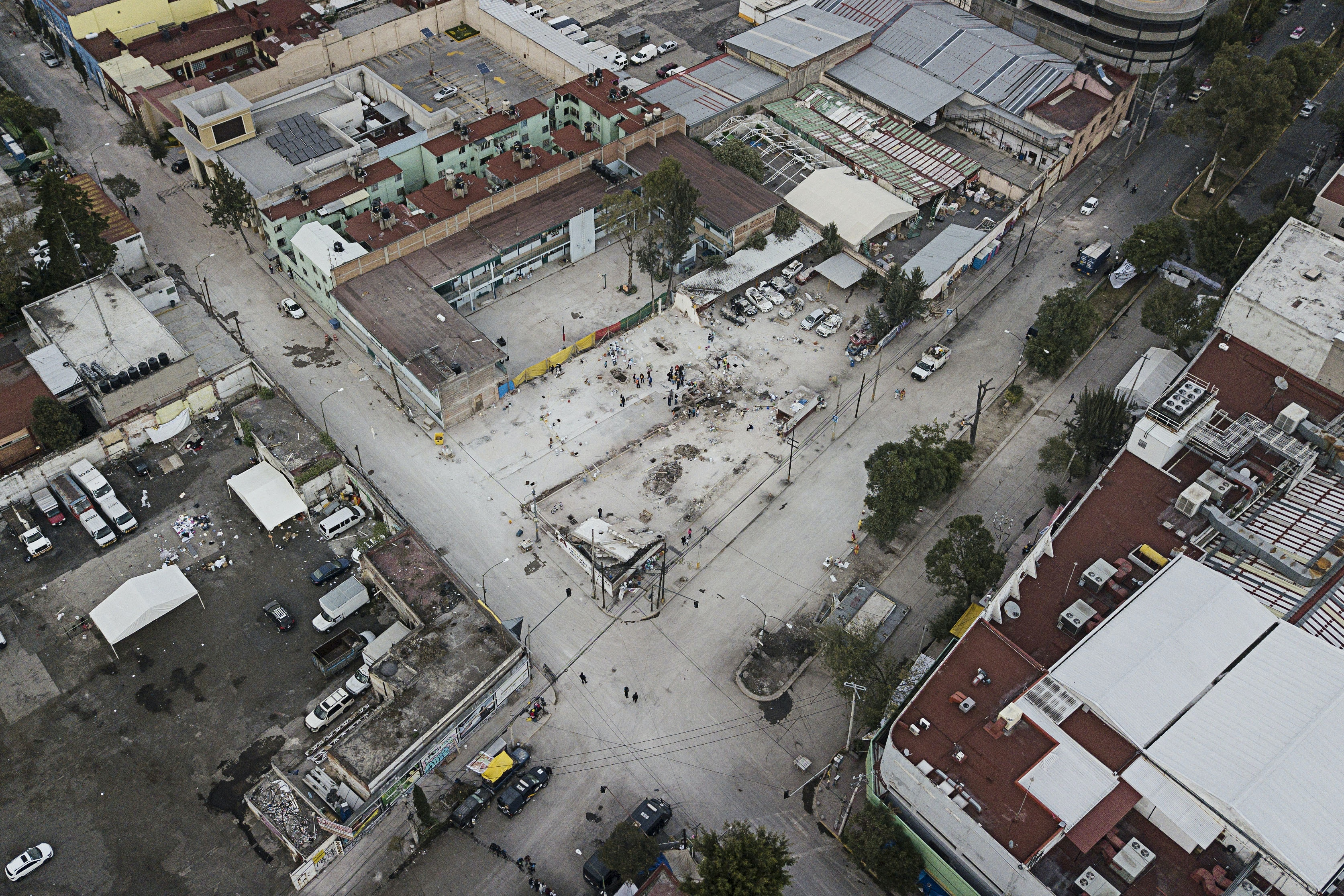The quake-collapsed textile factory building leaves an empty space at the corner of Bolivar and Chimalpopoca streets after the rubble was cleared away in the Obrera neighborhood of Mexico City, Saturday, Sept. 23, 2017. As rescue operations stretched into day 5, residents throughout the capital have held out hope that dozens still missing might be found alive. (AP Photo/Miguel Tovar)