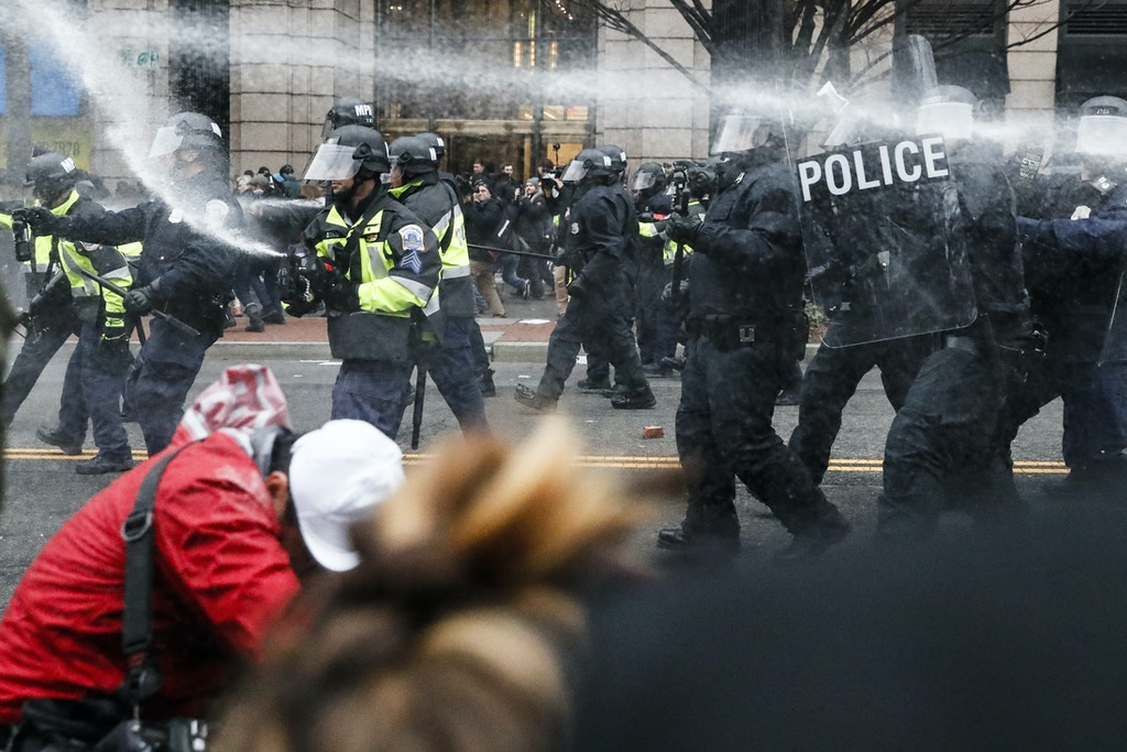 FILE- In this Jan. 20, 2017, file photo, police fire pepper spray at protestors during a demonstration in downtown Washington after the inauguration of President Donald Trump. A District of Columbia Superior Court ruled Thursday, Aug. 24, that an internet hosting company must turn over records for a website that the government alleges was used to plan violent protests on the day of President Donald Trump's inauguration. (AP Photo/John Minchillo, File)