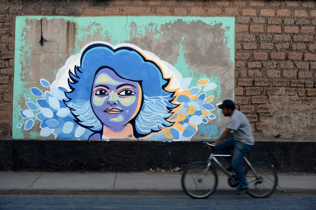 TOPSHOT - A man rides a bike past graffiti of Honduran indigenous environmentalist Berta Caceres a year after her murder, in La Esperanza, 180 km west of Tegucigalpa, on March 2, 2017. Caceres, an organizer of the Lenca people, the largest native group in Honduras, was murdered on March 3, 2016 in this city. / AFP PHOTO / ORLANDO SIERRA (Photo credit should read ORLANDO SIERRA/AFP/Getty Images)