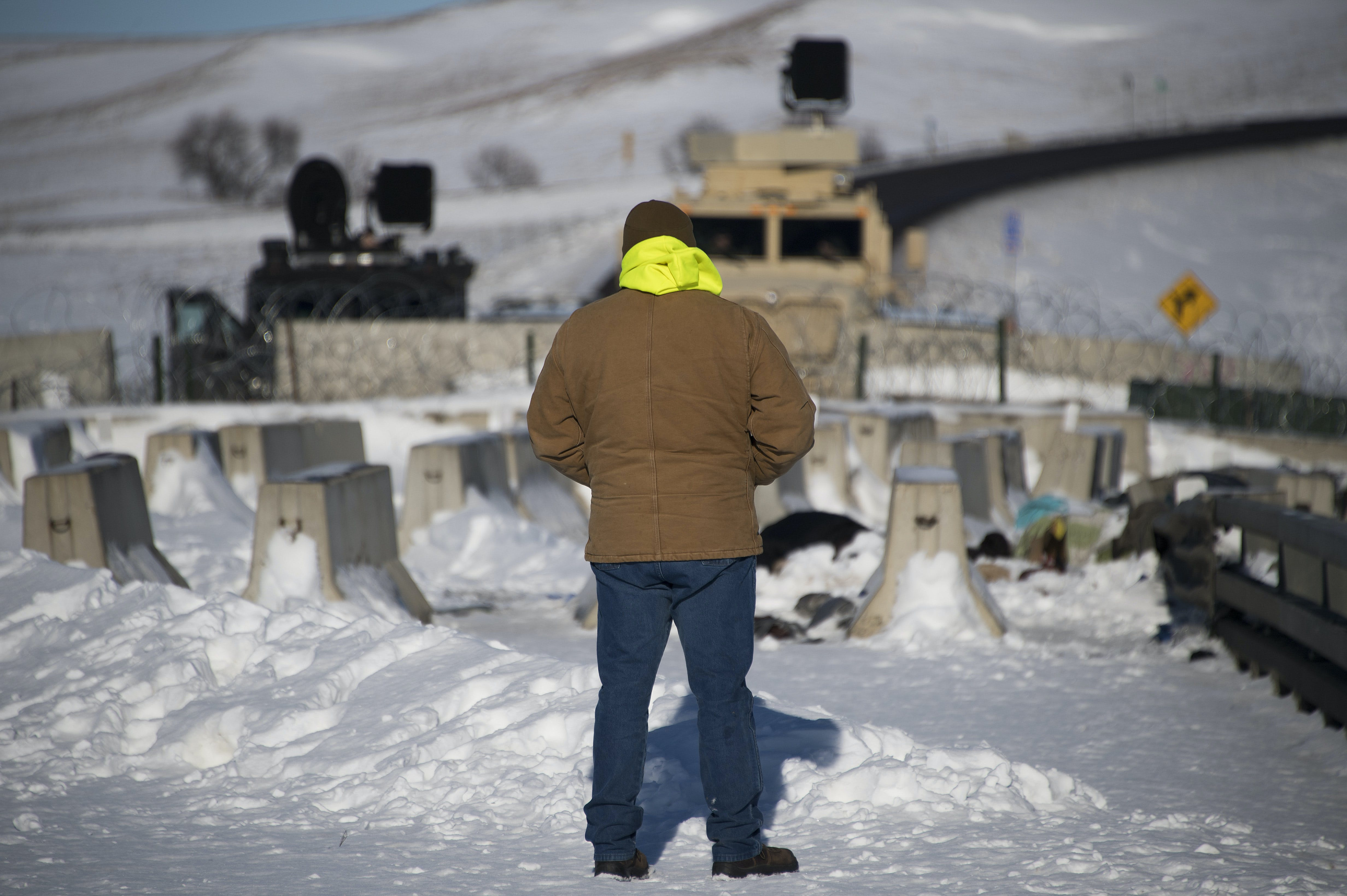 An activist stands alone in silent protest by a police barricade on a bridge near Oceti Sakowin Camp on the edge of the Standing Rock Sioux Reservation on December 4, 2016 outside Cannon Ball, North Dakota.Native Americans and activists from around the country gather at the camp trying to halt the construction of the Dakota Access Pipeline. / AFP / JIM WATSON (Photo credit should read JIM WATSON/AFP/Getty Images)