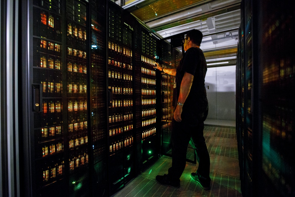 "HAMBURG, GERMANY - JUNE 07: An employee of the German Climate Computing Center (DKRZ, or Deutsches Klimarechenzentrum) poses next to the ""Mistral"" supercomputer, installed in 2016, at the German Climate Computing Center on June 7, 2017 in Hamburg, Germany. The DKRZ provides HPC (high performance computing) and associated services for climate research institutes in Germany. Its high performance computer and storage systems have been specifically selected with respect to climate and Earth system modeling. With a total of 100,000 processor cores, Mistral has a peak performance of 3.6 PetaFLOPS. With a capacity of 54 PBytes, its parallel file system is currently one of the largest in the world. The DKRZ's robot-operated tape archive has currently a capacity of 200 petabytes and allows for long-term archiving of climate simulations such as those carried out with respect to reports by the Intergovernmental Panel on Climate Change. (Photo by Morris MacMatzen/Getty Images)"