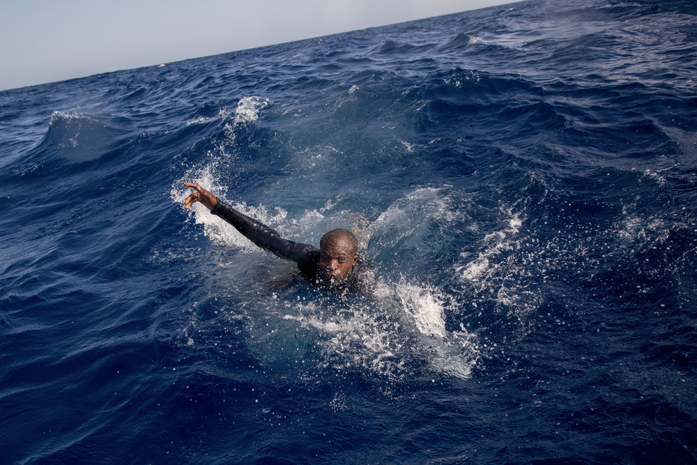 A migrant tries to board a boat of the German NGO Sea-Watch in the Mediterranean Sea on November 6, 2017.During a shipwreck, five people died, including a newborn child. According to the German NGO Sea-Watch, which has saved 58 migrants, the violent behavior of the Libyan coast guard caused the death of five persons. / AFP PHOTO / Alessio Paduano (Photo credit should read ALESSIO PADUANO/AFP/Getty Images)