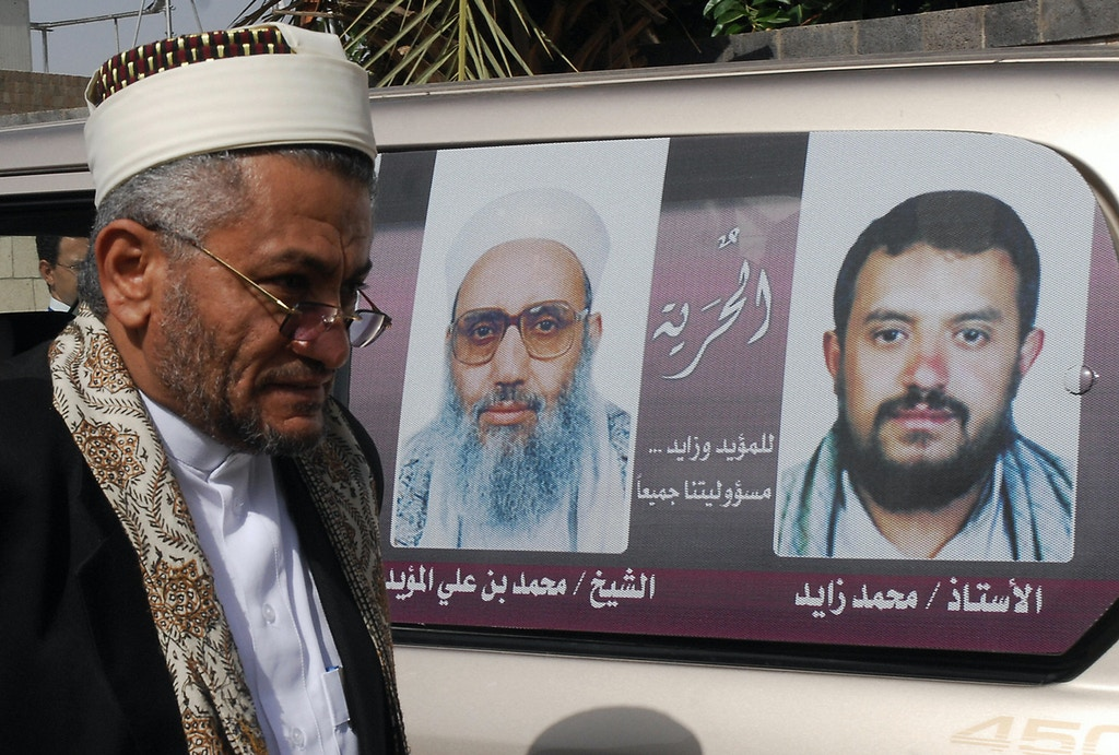 Yemeni Religious Endowments and Guidance Minister Hamud al-Hattar walks past pictures of Yemeni cleric Sheikh Mohammed Ali al-Moayad (L) and his assistant and bodyguard Mohammed Zayed (R) as he arrives to greet them at the airport in Sanaa on August 11, 2009 following their deportation from the US. Yemen staged a warm welcome for Moayad, expelled from the United States after originally being sentenced to 75 years in jail for supporting terrorism. The ailing Muslim cleric returned home after a US federal judge ordered his deportation, along with Zayed. AFP PHOTO/KHALED FAZAA (Photo credit should read KHALED FAZAA/AFP/Getty Images)