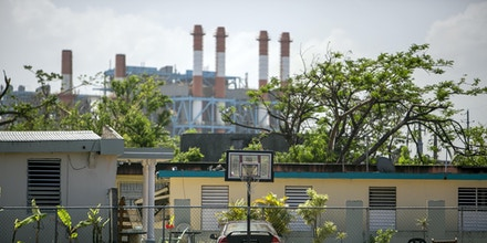 A basketball court is seen in front of the Puerto Rico Electric Power Authority (PREPA) Palo Seco plant in Palo Seco, Toa Baja, Puerto Rico, on Saturday, Oct. 21, 2017. For longer than most can remember, Puerto Ricans have paid some of the highest energy costs in the U.S. to a notoriously unreliable utility that neglected their grid for years and runs fossil-fuel plants that may be damaging their lungs. A month after Hurricane Maria devastated the island, power lines still lay slack along roads, utility poles are snapped clean in half, and most Puerto Ricans remain in the dark. Photographer: Xavier Garcia/Bloomberg via Getty Images