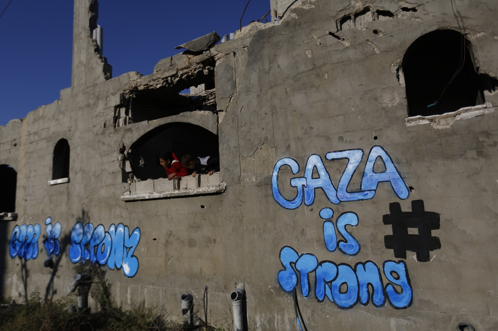 Palestinian children look out of the window of a destroyed building bearing graffiti in Gaza City's Al-Shejaiya suburb on December 25, 2014. AFP PHOTO / MOHAMMED ABED        (Photo credit should read MOHAMMED ABED/AFP/Getty Images)