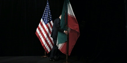 A staff removes the Iranian flag from the stage after a group picture with foreign ministers and representatives of Unites States, Iran, China, Russia, Britain, Germany, France and the European Union during the Iran nuclear talks at Austria International Centre in Vienna, Austria on July 14, 2015. Major powers clinched a historic deal aimed at ensuring Iran does not obtain the nuclear bomb, opening up Tehran's stricken economy and potentially ending decades of bad blood with the West.   AFP PHOTO / POOL / CARLOS BARRIA / AFP / POOL / CARLOS BARRIA        (Photo credit should read CARLOS BARRIA/AFP/Getty Images)