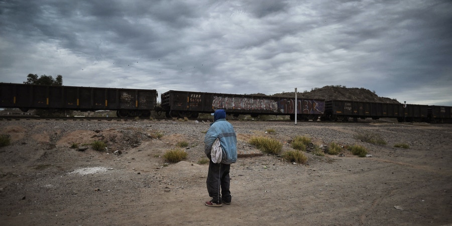 A Honduran migrant watches the train go by in the community of Caborca in Sonora state, Mexico, on January 13, 2017.Hundreds of Central American and Mexican migrants attempt to cross the US border daily. / AFP / ALFREDO ESTRELLA (Photo credit should read ALFREDO ESTRELLA/AFP/Getty Images)