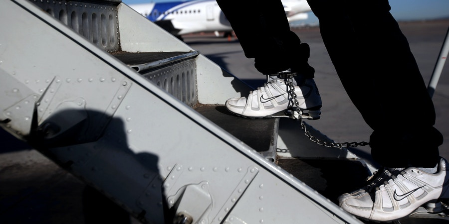 MESA, AZ - FEBRUARY 28:  A Honduran immigration detainee, his feet shackled and shoes laceless as a security precaution, boards a deportation flight to San Pedro Sula, Honduras on February 28, 2013 in Mesa, Arizona. U.S. Immigration and Customs Enforcement (ICE), operates 4-5 flights per week from Mesa to Central America, deporting hundreds of undocumented immigrants detained in western states of the U.S. With the possibility of federal budget sequestration, Most detainees typically remain in custody for several weeks before they are deported to their home country, while others remain for longer periods while their immigration cases work through the courts.  (Photo by John Moore/Getty Images)