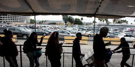 People line up on the pedestrian crossing lines on the Mexican side of the San Ysidro Port of Entry on November 1, 2017, in Tijuana, northwestern Mexico.After Donald Trump took office in January the trade in the border between US and Mexico have been affected by his anti-immigrant policies, many of the Mexicans that crossed to the US to shop cheaper, now refrain from doing so because of fear, anger or pride. / AFP PHOTO / GUILLERMO ARIAS / TO GO WITH AFP STORY by Javier TOVAR, with Said BETANZOS in Tijuana (Photo credit should read GUILLERMO ARIAS/AFP/Getty Images)