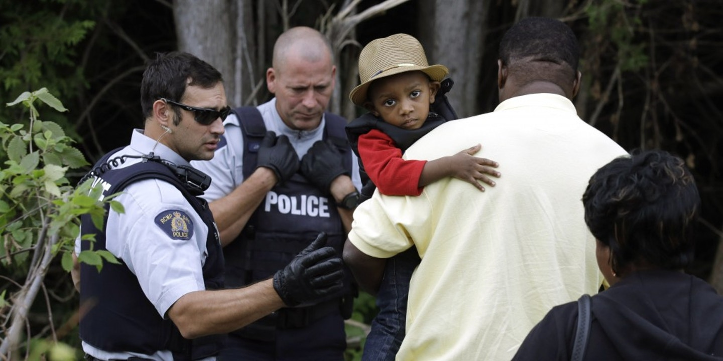 26348b65b4a9 A Haitian boy holds onto his father as they approach an illegally crossing  point, staffed