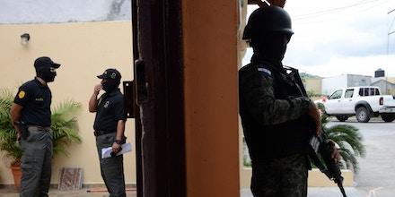 ntegrantes da Direção de Luta contra o Narcotráfico de Honduras (DLCN) e agentes das Forças Armadas participam de operação de apreensão de 32 imóveis, 15 veículos e nove empresas comerciais de seis oficiais de polícia hondurenhos acusados de participar de esquema de tráfico de drogas (Orlando Sierra/AFP/Getty Images)