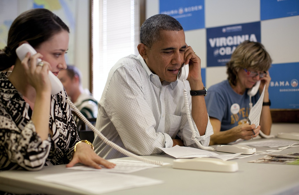 President Barack Obama makes phone calls to volunteers at an Organizing for America field office with Alexa Kissinger, left, and, Suzanne Stern, right,  Sunday, Oct. 14, 2012, in Williamsburg, Va. (AP Photo/Carolyn Kaster)
