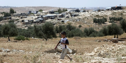 A Palestinian boy walks while backdropped by his home village of Susiya, south of the West Bank city of Hebron, Friday, July 24, 2015.  Residents of this dusty village are bracing for Israeli bulldozers to come and knock down their makeshift homes of tarp, wood and wire any day now. But as they wait for the military order to be carried out, villagers are rallying support from Western governments. (AP Photo/Nasser Nasser)
