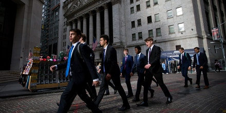 Pedestrians walk along Wall Street in front of the New York Stock Exchange (NYSE) in New York, U.S., on Monday, Oct. 23, 2017. U.S. stocks got off to a slow startas investors prepared for a big week of earnings reports, awaited possible changes at the Federal Reserve and monitored the progress of tax reform. Photographer: Michael Nagle/Bloomberg via Getty Images