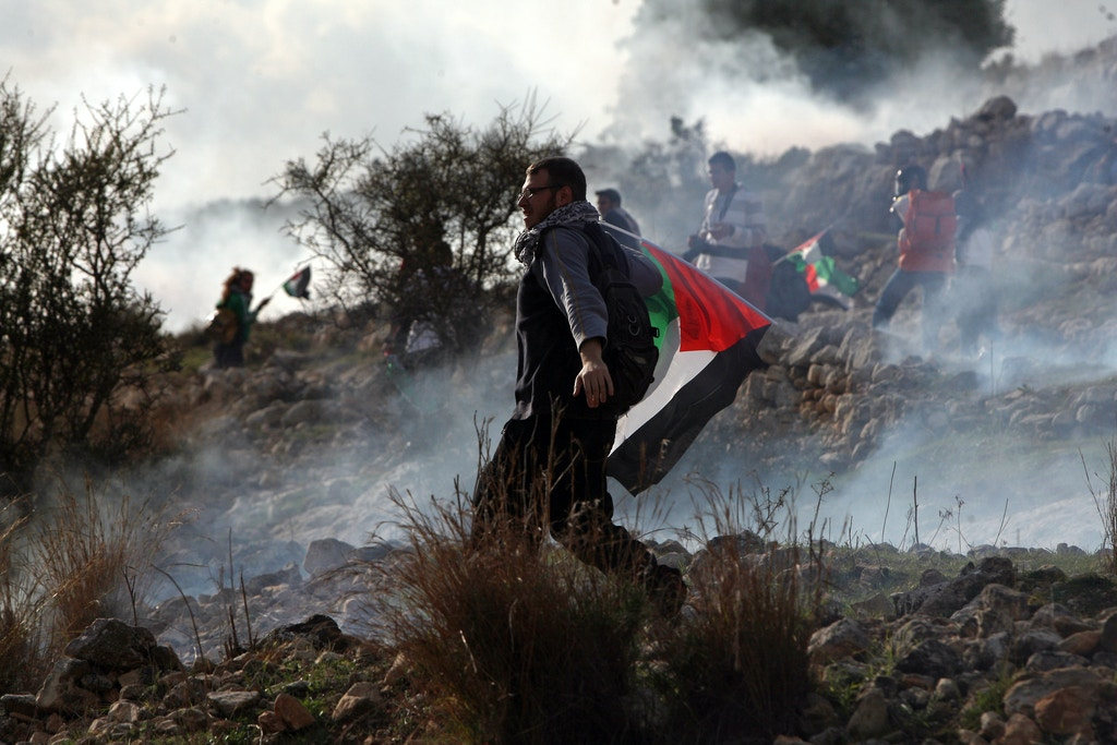 A Palestinian demonstrator holds his national flag as fellow protesters run for cover from tear gas fired by Israeli soldiers during a weekly protest against Israel's controversial separation barrier in the West Bank village of Nabi Saleh on December 16, 2011. AFP PHOTO/ABBAS MOMANI (Photo credit should read ABBAS MOMANI/AFP/Getty Images)