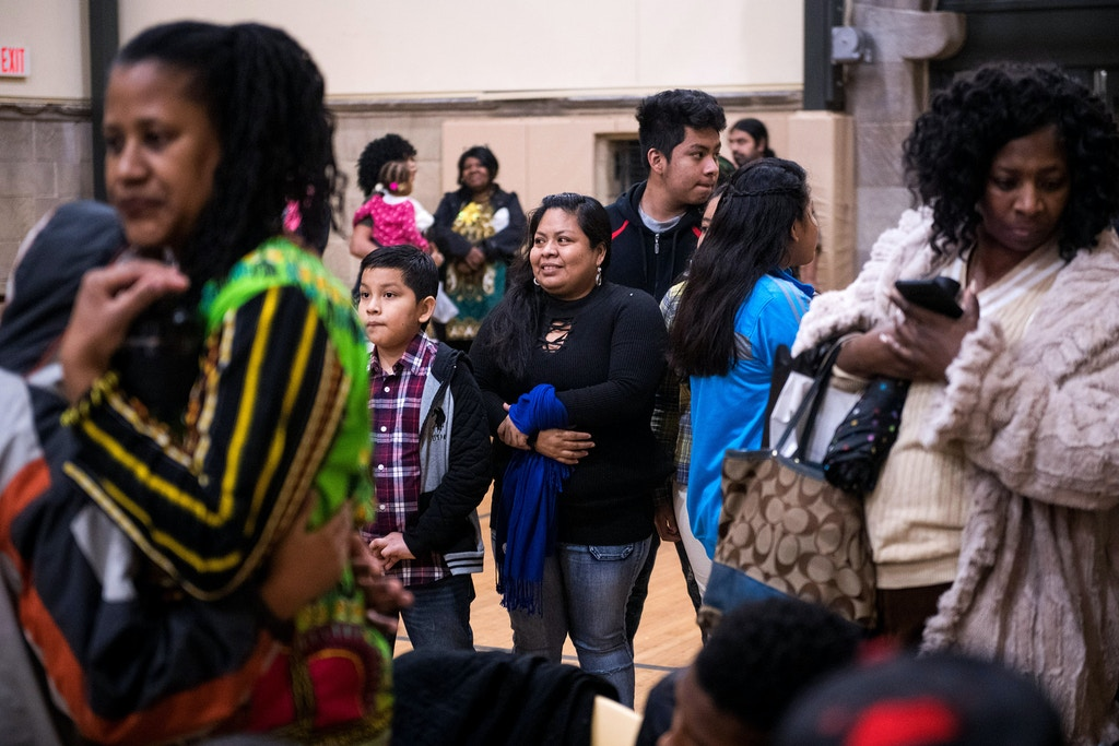 Carmela and her family watch a Kwanzaa celebration at the church. Carmela Hernandez, an undocumented Mexican immigrant who faces a deportation order along with her four children Fidel, 15, Kayri, 13, Joselyn, 11, and Edwin, 11, found temporary sanctuary from immigration officials by moving her family in early December into a small basement room at the historic African-American Church of the Advocate in North Philadelphia, Pennsylvania, December 23, 2017. Charles Mostoller for The Intercept