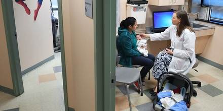 FALLS CHURCH, VA - OCTOBER 31: Ana Elsy Ramirez Diaz holds her son, Milan Rojas Ramirez as he is seen by Dr. Margaret-Anne Fernandez during a check-up visit at INOVA Cares Clinic for Children on Tuesday October 31, 2017 in Falls Church. A portion of the clinic's patients are insured through the Children's Health Insurance Program. (Photo by Matt McClain/The Washington Post via Getty Images)