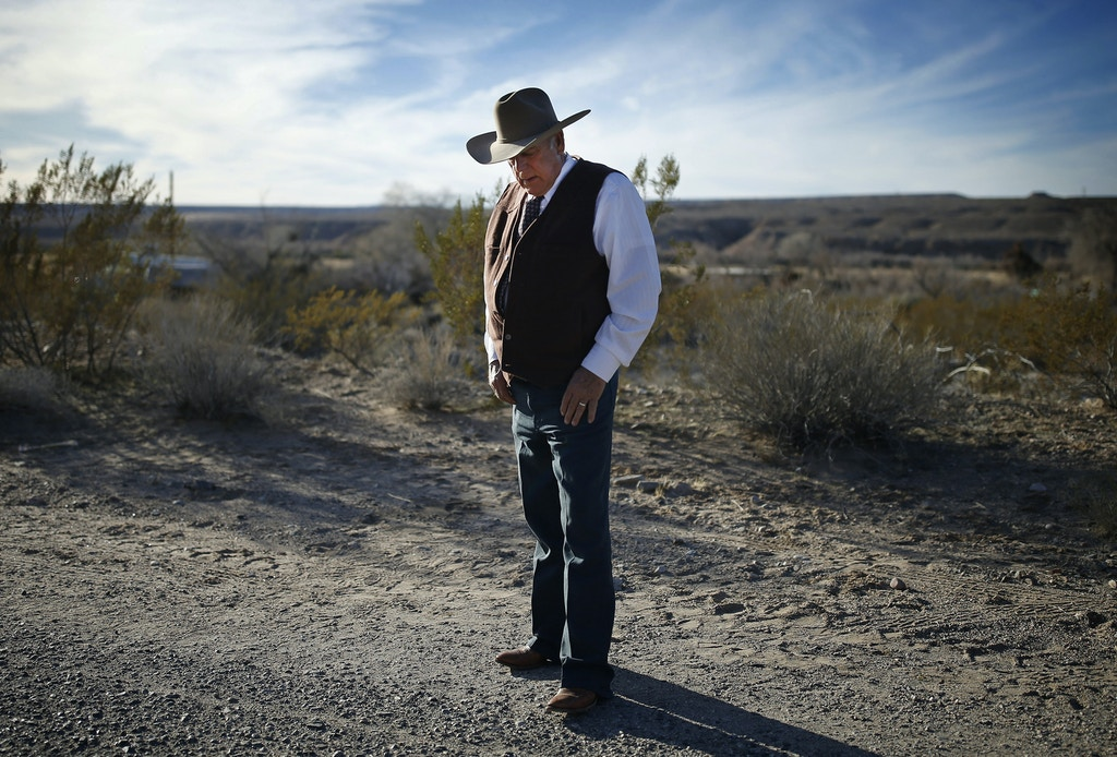 FILE - In this Jan. 27, 2016, file photo, rancher Cliven Bundy stands along the road near his ranch in Bunkerville, Nev. Bundy is expected to tell a judge on Thursday, March 10, whether he has hired a lawyer; enter a plea to charges in a 16-count indictment filed March 2 against him and 18 other people; and seek release pending trial on a date yet to be set. (AP Photo/John Locher, File)