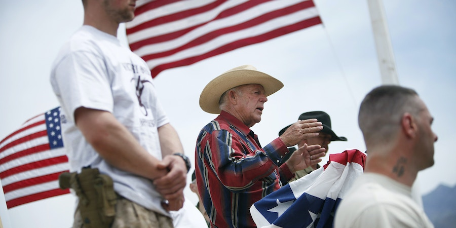 FILE - In this April 18, 2014, file photo, flanked by armed supporters, rancher Cliven Bundy speaks at a protest camp near Bunkerville, Nev. A U.S. judge has set a Jan. 8, 2018, date to decide whether charges should be dismissed outright in the prosecution of Cliven Bundy, sons Ryan and Ammon Bundy, and Montana militia leader Ryan Payne. They're charged with organizing and leading an armed uprising against federal agents to stop a roundup of Bundy cattle near the Nevada town of Bunkerville in April 2014. (John Locker /Las Vegas Review-Journal via AP, File)