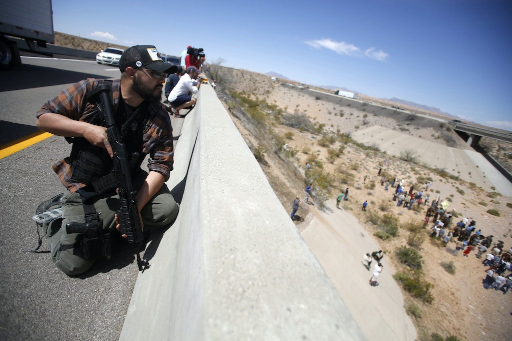 Eric Parker from central Idaho stands watch on a bridge with his weapon as protesters gather by the Bureau of Land Management's base camp, where cattle that were seized from rancher Cliven Bundy are being held, near Bunkerville, Nevada April 12, 2014. The U.S. Bureau of Land Management on Saturday said it had called off an effort to round up Bundy's herd of cattle that it had said were being illegally grazed in southern Nevada, citing concerns about safety. The conflict between Bundy and U.S. land managers had brought a team of armed federal rangers to Nevada to seize the 1,000 head of cattle. REUTERS/Jim Urquhart (UNITED STATES - Tags: ANIMALS CIVIL UNREST AGRICULTURE CRIME LAW TPX IMAGES OF THE DAY) - GM1EA4D0BDM01