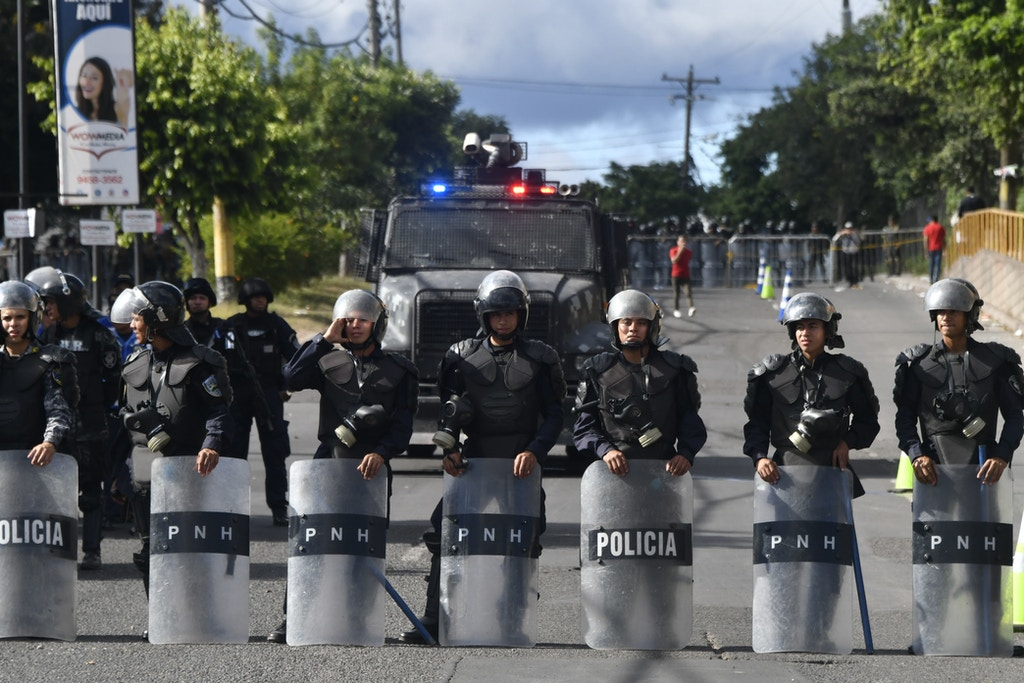 Honduran military police stand guard next to supporters of opposition candidate Salvador Nasralla as they hold a protest march on December 3, 2017 in Tegucigalpa, despite the state of emergency and a 10-day curfew imposed by the government to stop violent demonstrations triggered by claims of presidential election fraud. Honduras aims to resume the vote count to define the winner of the November 26 elections between President Juan Orlando Hernandez and the opposition candidate Salvador Nasralla. One young woman was killed and at least 12 civilians have been wounded during violent clashes sparked by Nasralla's call for his supporters to take to the streets. / AFP PHOTO / JOHAN ORDONEZ (Photo credit should read JOHAN ORDONEZ/AFP/Getty Images)