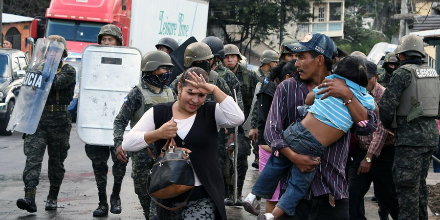 TOPSHOT - Residents get away from clashes between riot police and supporters of opposition candidate Salvador Nasralla, during protests in Tegucigalpa, on December 18, 2017.Honduran President Juan Orlando Hernandez is declared the winner of a heavily disputed presidential election held three weeks ago, despite mounting protests and opposition claims of fraud. / AFP PHOTO / ORLANDO SIERRA (Photo credit should read ORLANDO SIERRA/AFP/Getty Images)