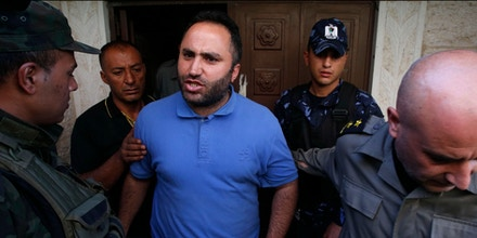 Issa Amro (C) a prominent Palestinian activist and founder of Youth Against Settlements is lead by Palestinian security forces out of the court in the West Bank town of Hebron on September 7, 2017, after the Palestinian Authority extended his detention for criticising their arrest of a journalist on social media.Amro's detention was extended for another four days, while the prosecution called for him to be charged for