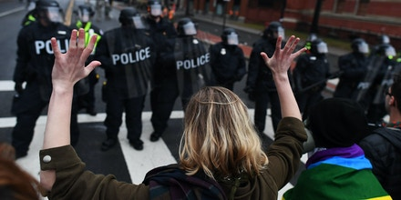 An anti-Trump protester holds her hands up as police officers lineup in Washington, DC, on January 20, 2017. Masked, black-clad protesters carrying anarchist flags smashed windows and scuffled with riot police Friday in downtown Washington, blocks away from the route of the parade in honor of newly sworn-in President Donald Trump. Washington police arrested more than 90 people over acts of vandalism committed on the fringe of peaceful citywide demonstrations being held against Trump's inauguration. / AFP / Jewel SAMAD (Photo credit should read JEWEL SAMAD/AFP/Getty Images)