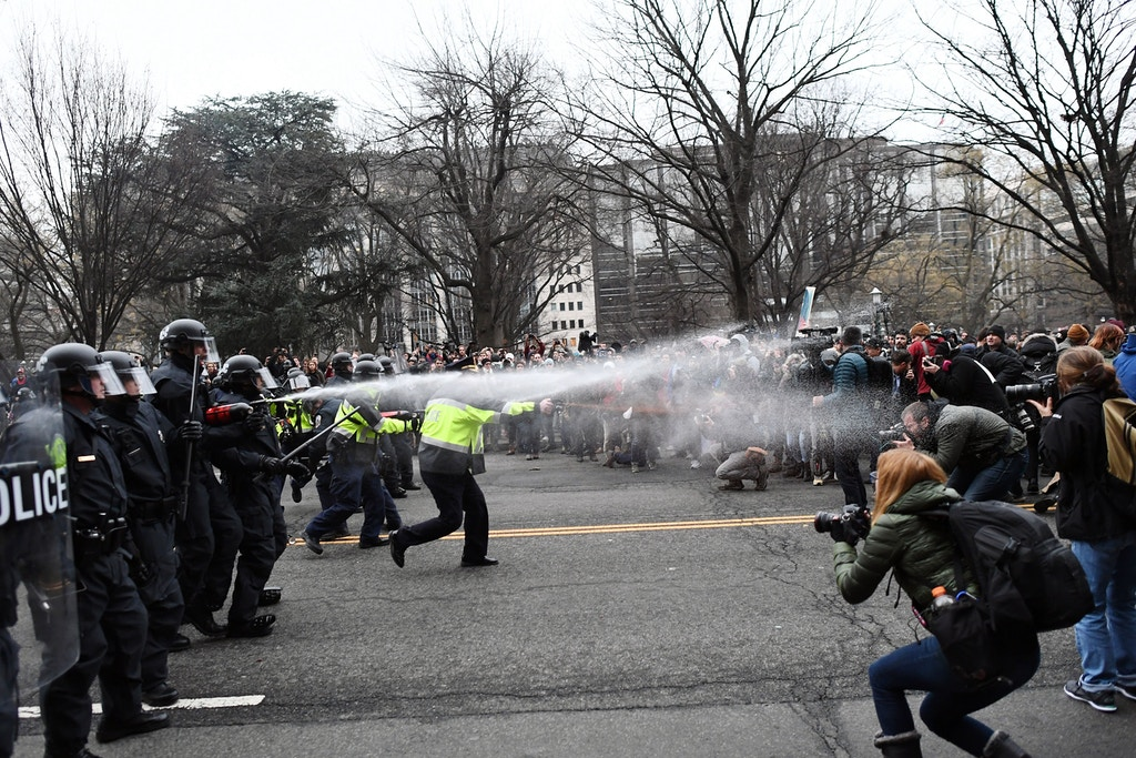 Police pepper spray at anti-Trump protesters during clashes in Washington, DC, on January 20, 2017. Masked, black-clad protesters carrying anarchist flags smashed windows and scuffled with riot police Friday in downtown Washington, blocks away from the route of the parade in honor of newly sworn-in President Donald Trump. Washington police arrested more than 90 people over acts of vandalism committed on the fringe of peaceful citywide demonstrations being held against Trump's inauguration. / AFP PHOTO / Jewel SAMAD (Photo credit should read JEWEL SAMAD/AFP/Getty Images)