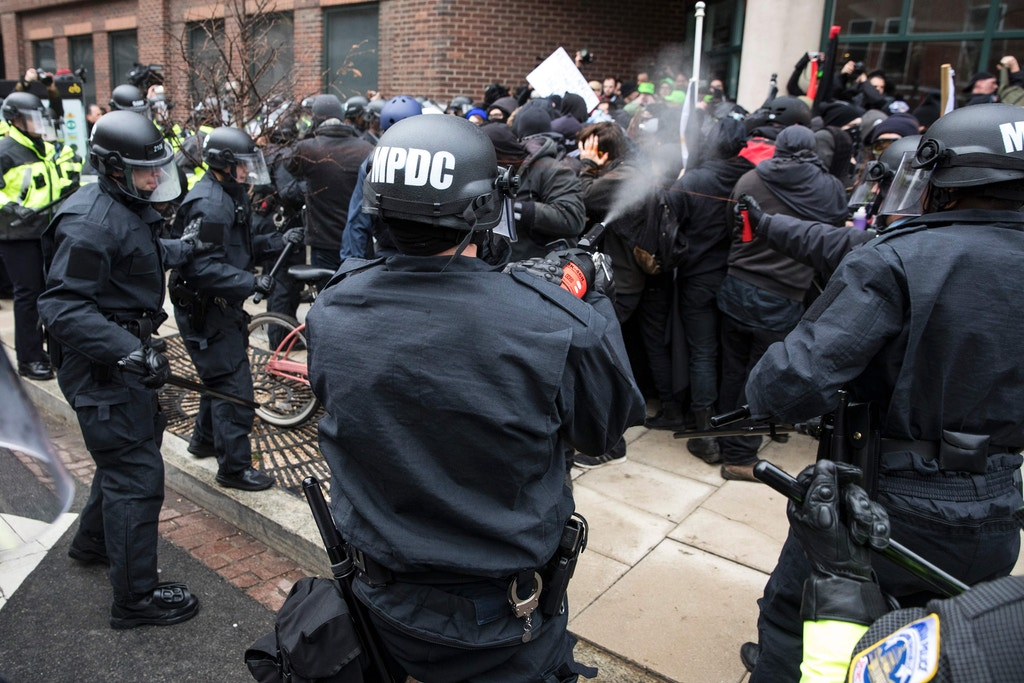 TOPSHOT - Police officers pepper spray a group of protestors before the inauguration of President-elect Donald Trump January 20, 2017 in Washington, DC. Donald Trump was sworn in as the 45th president of the United States Friday -- capping his improbable journey to the White House and beginning a four-year term that promises to shake up Washington and the world. / AFP / ZACH GIBSON (Photo credit should read ZACH GIBSON/AFP/Getty Images)