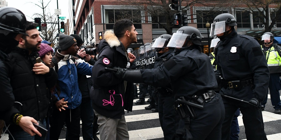 Police officers push back demonstrators as they protest against US President Donald Trump in Washington, DC, on January 20, 2017. Masked, black-clad protesters carrying anarchist flags smashed windows and scuffled with riot police Friday in downtown Washington, blocks away from the route of the parade in honor of newly sworn-in President Donald Trump. Washington police arrested more than 90 people over acts of vandalism committed on the fringe of peaceful citywide demonstrations being held against Trump's inauguration. / AFP / Jewel SAMAD (Photo credit should read JEWEL SAMAD/AFP/Getty Images)