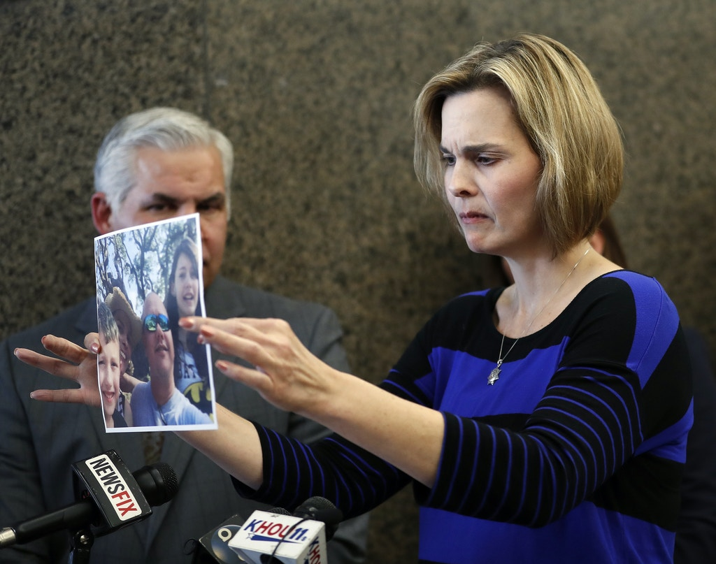 Kathleen Goforth, widow of Harris County Sheriff's Deputy Darren Goforth, holds up a photo of her late husband as she spoke to the media after Shannon Miles pled guilty at the Harris County Civil Courthouse, Wednesday, Sept. 13, 2017, in Houston. Miles, accused of fatally shooting Goforth, pleaded guilty Wednesday to capital murder and was sentenced to life in prison without the possibility of parole. (Karen Warren/Houston Chronicle via AP)